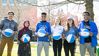 Student on Campus holding Blue and White Basketballs