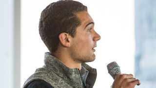 Mario Damasceno, a junior in the Stillman School of Business speaking into a microphone.