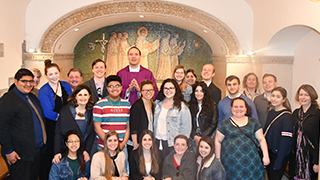 Picture of students and priest in front of a mural