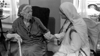 Dorothy Day and Mother Teresa sitting and holding hands.