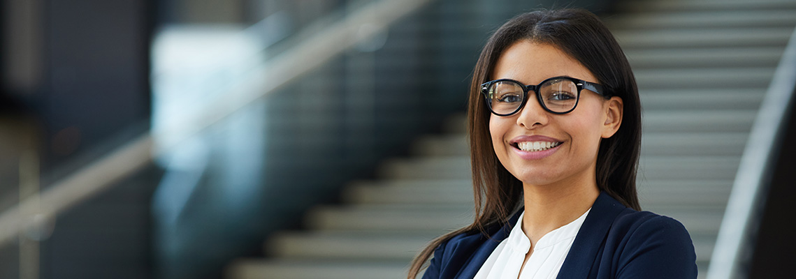 Woman wearing glasses smiling at camera.