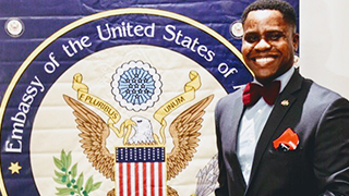 Erick Agbleke posing with US Embassy of Togo Flag x320