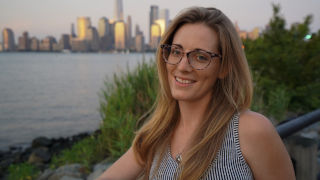 Headshot of Meg Reilly with the New York City skyline in the background