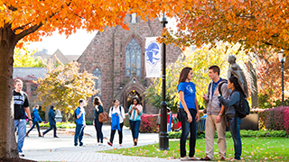 Students walking and talking on campus during a Fall day.