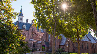 Side view of President's Hall and the Chapel with sun shining through trees.