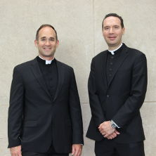 Fr. Laracy and Fr. Platania in McNulty Hall behind the mural of the cosmos.