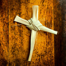 A cross made out of palms, laying on a piece of wood.