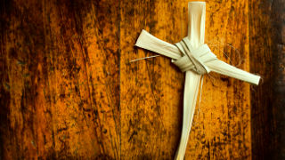 A cross made out of palms laying on a piece of wood.
